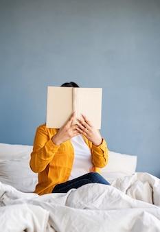 Café da manhã e rotina matinal. jovem morena sentada na cama comendo croissants e lendo um livro