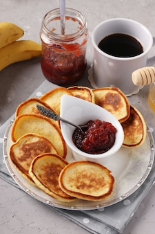Café da manhã em casa: panquecas com geleia, mel, bananas e uma xícara de café em um guardanapo cinza sobre fundo de concreto