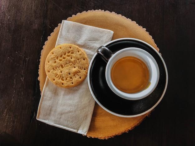 Café da manhã em copo preto e biscoitos na tábua de madeira