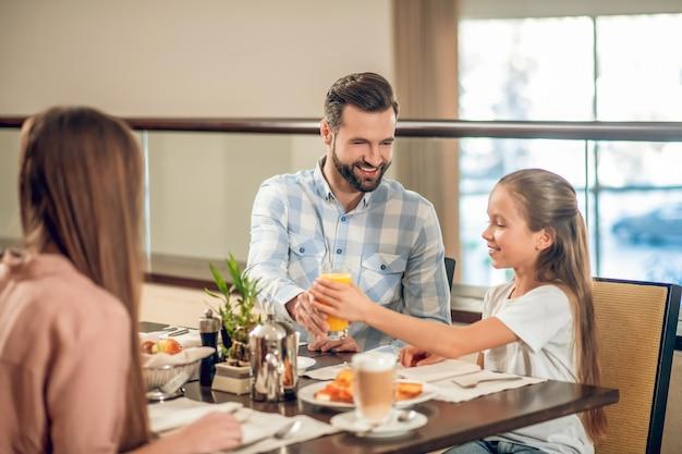 Café da manhã em família. filhos e o pai sentados à mesa do restaurante