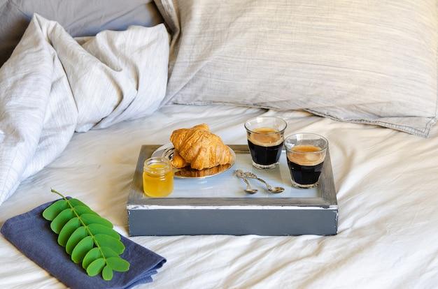 Café da manhã em lençóis cinza. duas xícaras de café e croissants com geléia. conceito de surpresa de bom dia. estilo escandinavo.