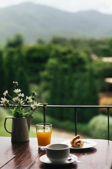 Café da manhã em mesa de madeira com vista natural