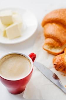 Café da manhã em um copo vermelho, croissants e manteiga no fundo branco