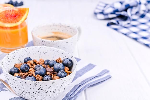 Café da manhã em um fundo branco de madeira. muesli com frutas e suco de laranja. copie o espaço