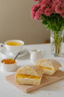 Café da manhã ensolarado. torrada com geléia de laranja e chá. comida caseira.