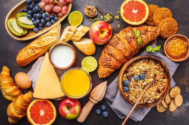 Café da manhã equilibrado saudável em um fundo escuro. muesli, leite, suco, croissants, queijo, biscoitos.