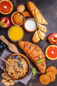 Café da manhã equilibrado saudável em um fundo escuro. muesli, leite, suco, croissants.