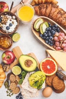 Café da manhã equilibrado saudável no fundo branco. muesli, suco, croissants, queijo, biscoitos e frutas, vista superior.