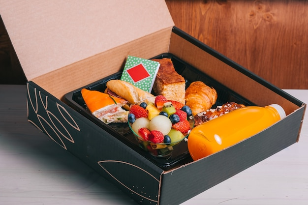 Café da manhã espanhol com delivery de salmão, presunto ibérico, queijo e suco de laranja em caixa de papelão entrega segura