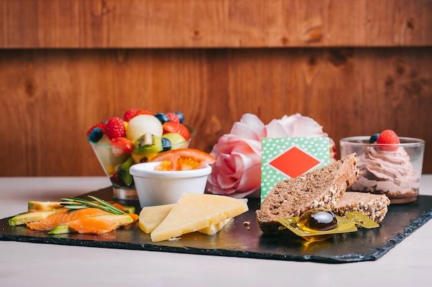 Café da manhã espanhol com suco de laranja, salmão e jamon, queijo, tomate com fatias de pão preto em um prato preto. parede de madeira