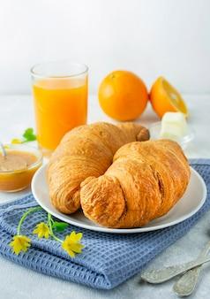 Café da manhã europeu com croissants frescos, geléia e suco de laranja. café da manhã em uma mesa de luz, vista lateral. fundo de comida.