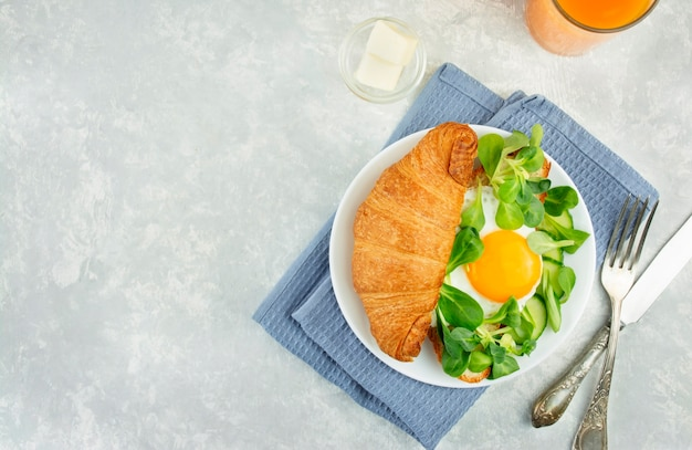 Café da manhã europeu com croissants frescos, ovos fritos, ervas e suco de laranja. café da manhã em uma mesa de luz, vista de cima. fundo alimentar