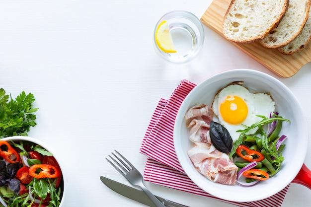 Café da manhã europeu: ovo em forma de coração, bacon, feijão verde em uma mesa branca. foco seletivo. vista de cima. copie o espaço.