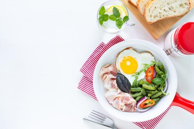 Café da manhã europeu: ovo em forma de coração, bacon, feijão verde em uma mesa branca. foco seletivo. vista de cima. copie o espaço