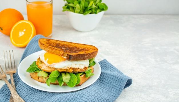 Café da manhã europeu, sanduíche com ovo frito, frango, ervas e suco de laranja. café da manhã em uma mesa de luz, vista de cima. fundo de comida.