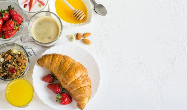 Café da manhã feito com croissant, mel, morangos, café, suco de laranja e granola
