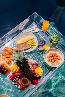 Café da manhã flutuante em incrível villa de hotel na piscina azul