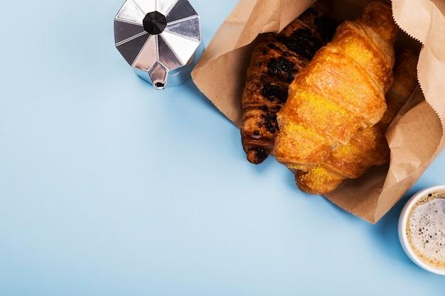 Café da manhã francês - café e croissants em saco de papel no espaço azul. entrega de produtos. vista superior, espaço de cópia