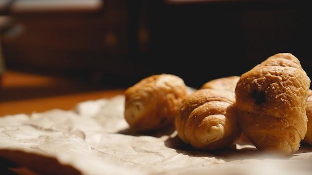 Café da manhã francês com croissant, louças kraft em papel kraft. mini croissants