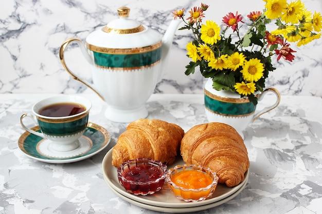 Café da manhã francês com croissants, geléia de damasco, geléia de cereja e uma xícara de chá, flores vermelhas e amarelas