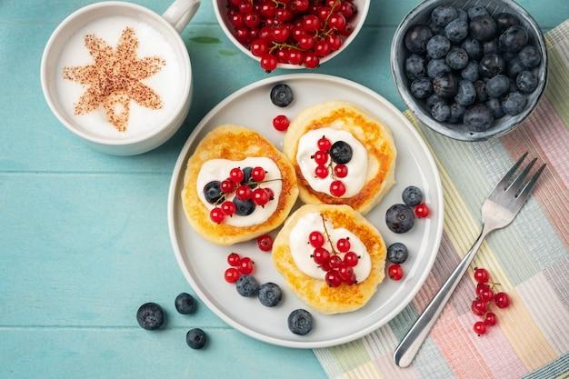 Café da manhã fresco e saboroso: panquecas de queijo cottage com groselha e mirtilo.