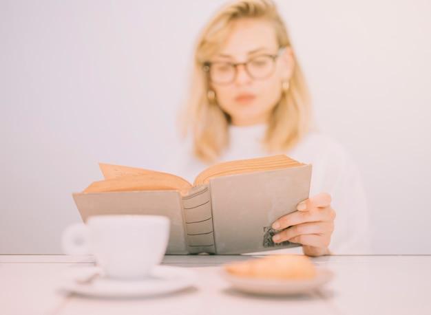 Café da manhã fresco na frente da empresária jovem defocussed lendo o livro