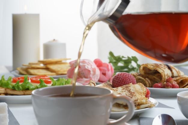 Café da manhã fresco, saboroso com um sanduíche e chá em um fundo claro.
