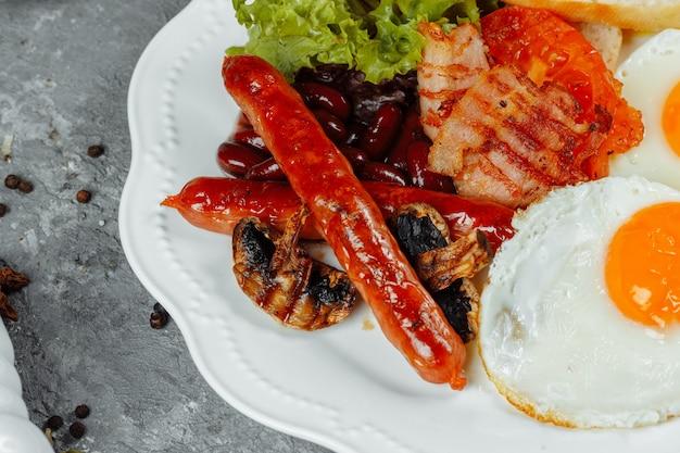 Café da manhã frito com bacon, linguiça e feijão cozido.