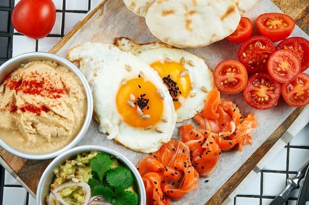 Café da manhã incomum. ovos fritos, tomate cereja, hummus guacamole e salmão com pão árabe em uma placa em uma mesa branca. comida de vista superior.