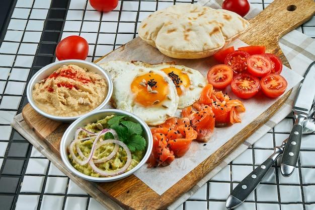 Café da manhã incomum. ovos fritos, tomate cereja, hummus guacamole e salmão com pão árabe em uma placa em uma mesa branca. feche os alimentos.