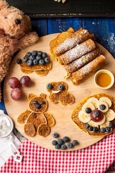 Café da manhã infantil. panquecas com frutas e guerreiros, com rostos alegres. vista do topo.