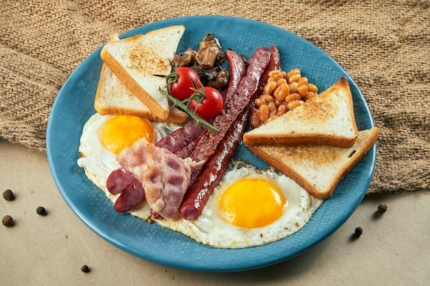 Café da manhã inglês clássico: torradas, linguiças defumadas, bacon, ovos fritos, feijão e torradas fritas num prato azul. feche acima da vista. lay plana de alimentos