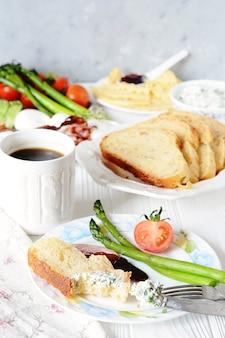 Café da manhã inglês com ovo escalfado, torrada de aspargos e bacon