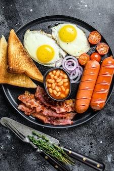 Café da manhã inglês com ovos fritos, linguiça, bacon, feijão e torradas em um prato.