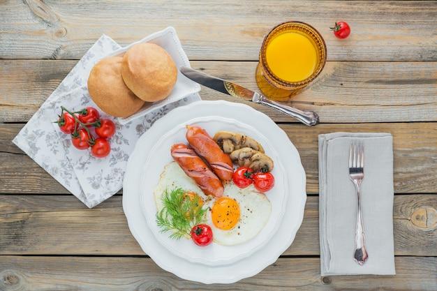 Café da manhã inglês com ovos fritos, salsichas, cogumelos, tomates grelhados e suco de laranja fresco na mesa de madeira rústica.