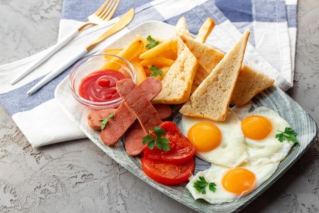Café da manhã inglês com ovos, salsichas, torradas francesas e fatias de batata na mesa cinza