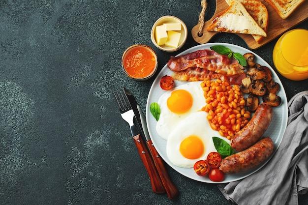 Café da manhã inglês completo em prato com ovos fritos, linguiça, bacon, feijão, torradas e café. vista de cima.