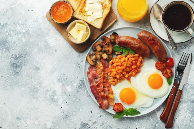 Café da manhã inglês completo em um prato com ovos fritos, salsichas, bacon, feijão, torradas e café na luz de fundo de pedra. com espaço de cópia. vista do topo.