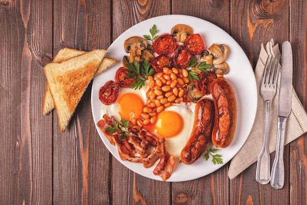 Café da manhã inglês completo tradicional com ovos fritos, salsichas, feijão, cogumelos, tomates grelhados e bacon em fundo de madeira. vista do topo