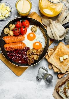 Café da manhã inglês. diversos petiscos com suco de laranja. sobre um fundo rústico.