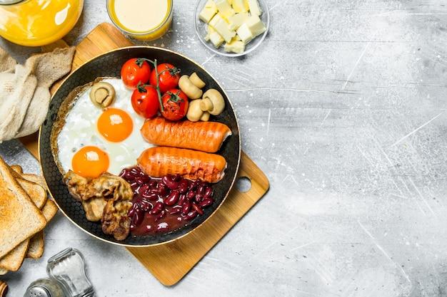 Café da manhã inglês. diversos petiscos com suco de laranja. sobre uma superfície rústica.