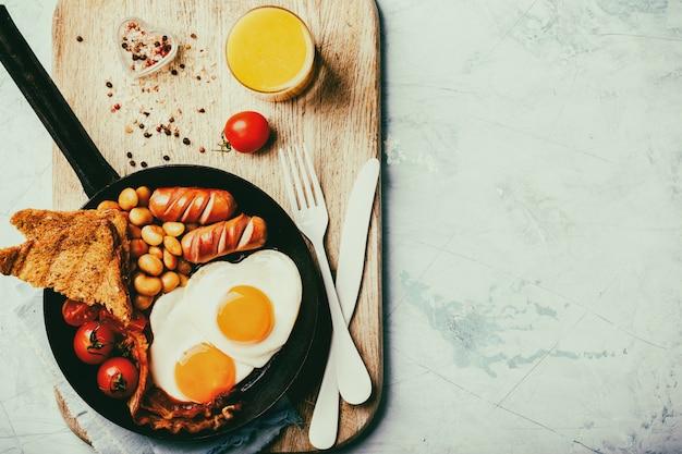 Café da manhã inglês em uma frigideira. ovos em forma de coração