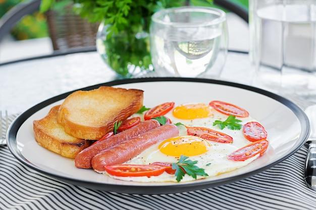 Café da manhã inglês no terraço de verão: ovos fritos, linguiça, tomate e torradas. xícara de café. feche acima do café da manhã do hotel.