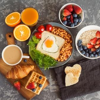 Café da manhã inglês: ovo frito, feijão e torradas em um prato com tomate cereja, salada, suco, frutas e croissant