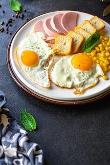 Café da manhã inglês, ovo frito, pão torrado, legumes, milho, queijo e mais pronto para comer na mesa