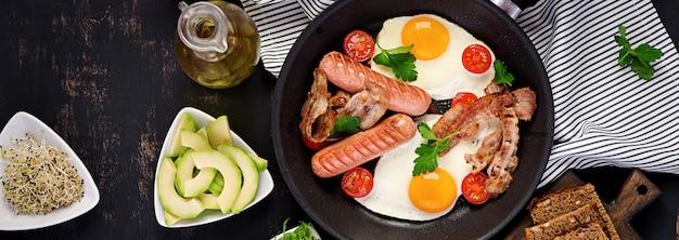 Café da manhã inglês - ovo frito, tomate, linguiça e bacon. vista do topo
