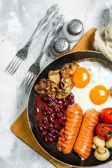 Café da manhã inglês. ovos fritos com linguiça, bacon e feijão. sobre uma superfície rústica.