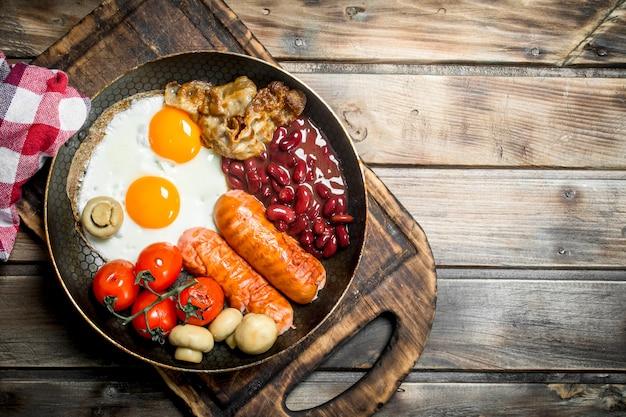 Café da manhã inglês. ovos fritos com linguiça, bacon e feijão vermelho em lata. sobre uma superfície de madeira.