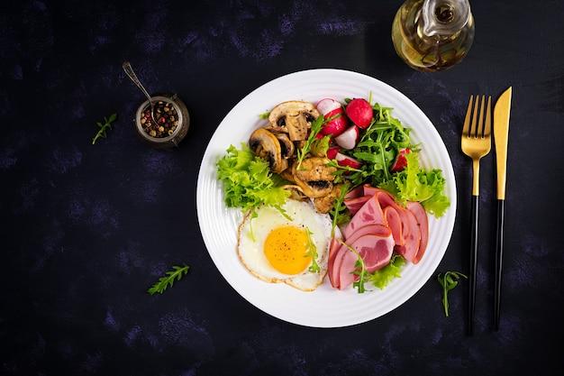 Café da manhã inglês - ovos fritos, presunto, cogumelos fritos, rabanete e rúcula
