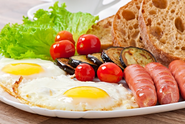 Café da manhã inglês - ovos fritos, salsichas, berinjela e tomate